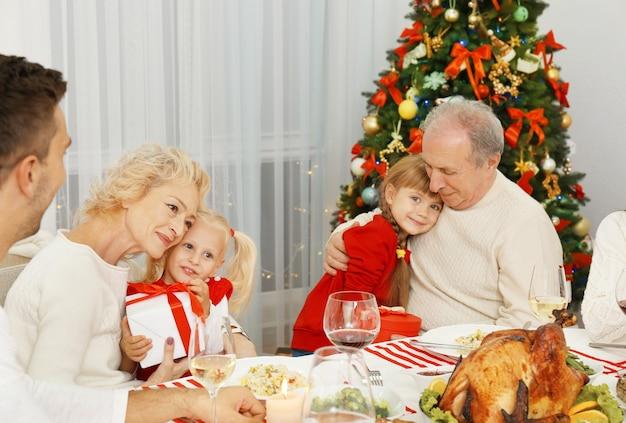 Gelukkige familie met kerstdiner in de woonkamer