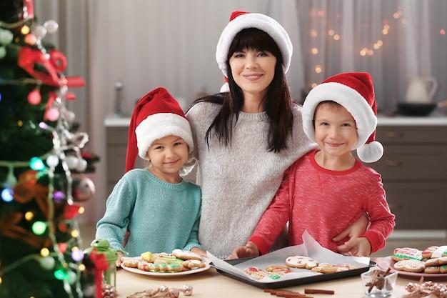 Gelukkige familie met kerstkoekjes in de keuken