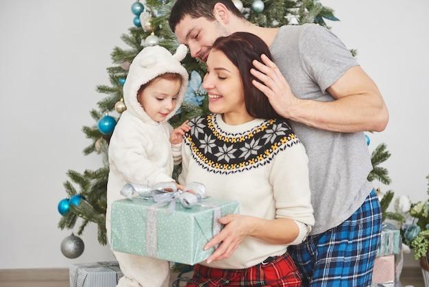 Gelukkige familie met kerstmis in ochtend die giften samen dichtbij de spar openen. het concept van gezinsgeluk en welzijn