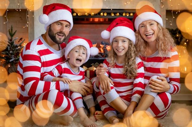 Gelukkige familie met kinderen die gestreepte pyjama's dragen dichtbij open haard met kerstmis. moeder, vader en kinderen hebben plezier thuis. xmas vakantie concept