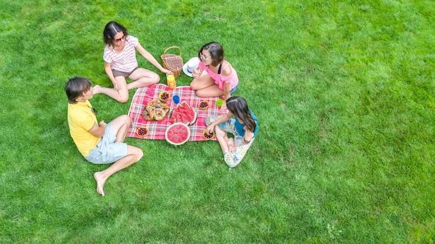 Gelukkige familie met kinderen die picknick in park hebben, ouders met jonge geitjes die op tuingras zitten en gezonde maaltijd in openlucht eten