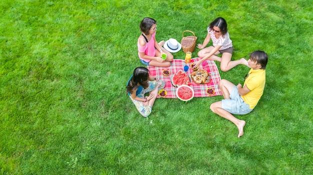 Gelukkige familie met kinderen met picknick in het park, ouders met kinderen zittend op tuingras en gezonde maaltijden buitenshuis eten, luchtfoto drone weergave van bovenaf, familievakantie en weekend concept