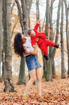 Gelukkige familie met klein schattig kind in park op geel blad met grote pompoen in de herfst