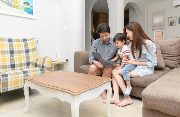 Gelukkige familie met kleine kinderen die samen van laptop genieten
