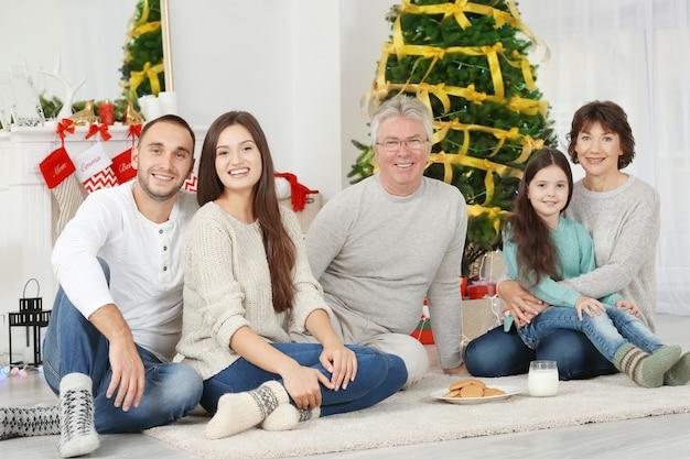 Gelukkige familie met koekjes en melk in woonkamer ingericht voor kerstmis