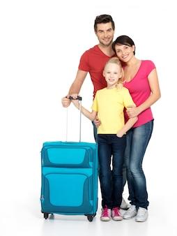 Gelukkige familie met koffer bij studio die op witte achtergrond wordt geïsoleerd