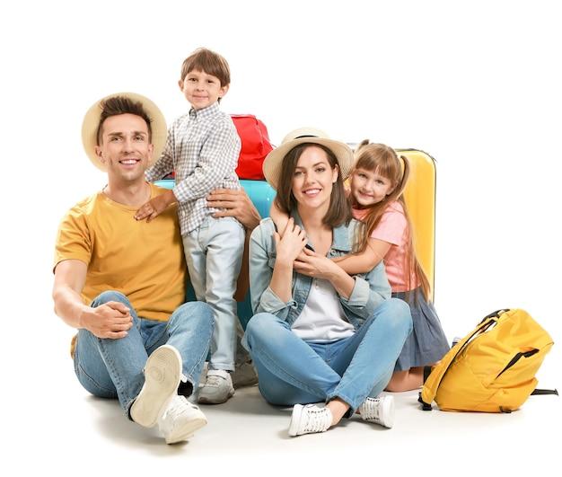 Gelukkige familie met koffers op wit wordt geïsoleerd