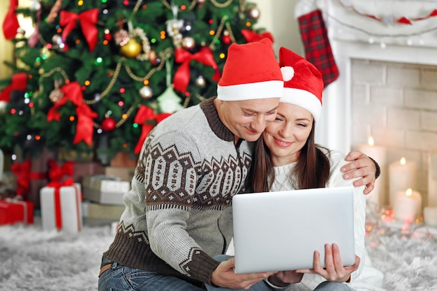 Gelukkige familie met laptop op kerstboom