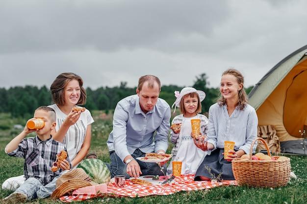 Gelukkige familie met picknick in de weide op een zonnige dag. familie genieten van kampeervakantie op het platteland.