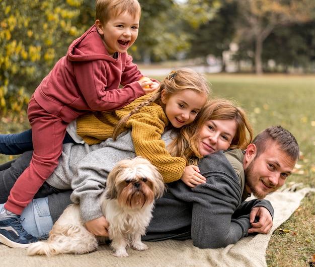 Gelukkige familie met schattige hond in de natuur