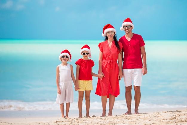 Gelukkige familie met twee kinderen in santa hat op zomervakantie