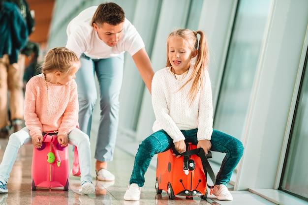 Gelukkige familie met twee kinderen op de luchthaven veel plezier bij het wachten op instappen