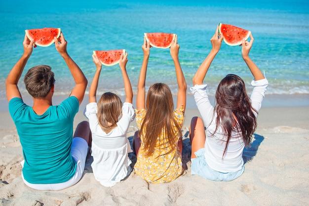 Gelukkige familie met watermeloen op het strand. kleine kinderen en hun ouders aan de kust plezier hebben.