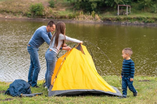 Gelukkige familie met zoontje opgezet camping tent. gelukkige jeugd, kampeertrip met ouders. een kind helpt een tent op te zetten