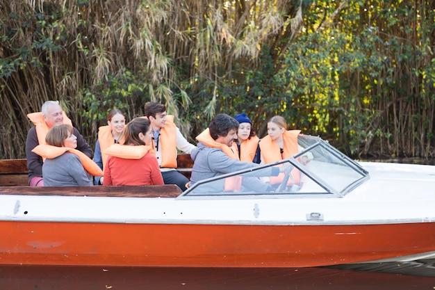 Gelukkige familie met zwemvesten varen op de rivier