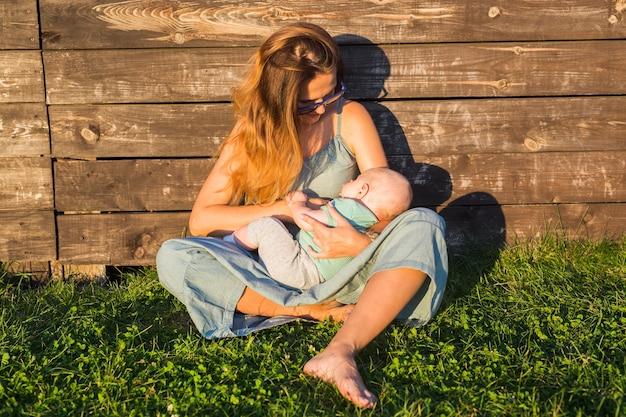 Gelukkige familie moeder en baby knuffelen op aard in de zomer