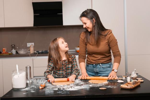Gelukkige familie, moeder en dochter die deeg voorbereiden om wat koekjes te maken en glimlachen