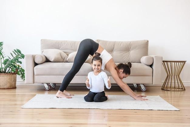 Gelukkige familie moeder en dochter doen yoga op het tapijt thuis