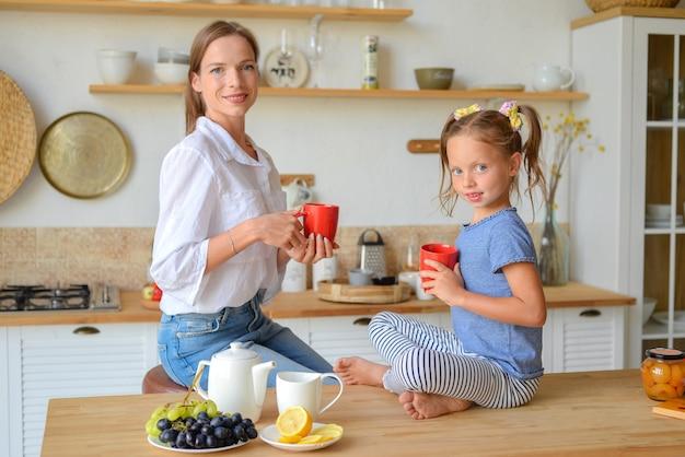 Gelukkige familie moeder en dochter drinken thee in de keuken familie ontbijt