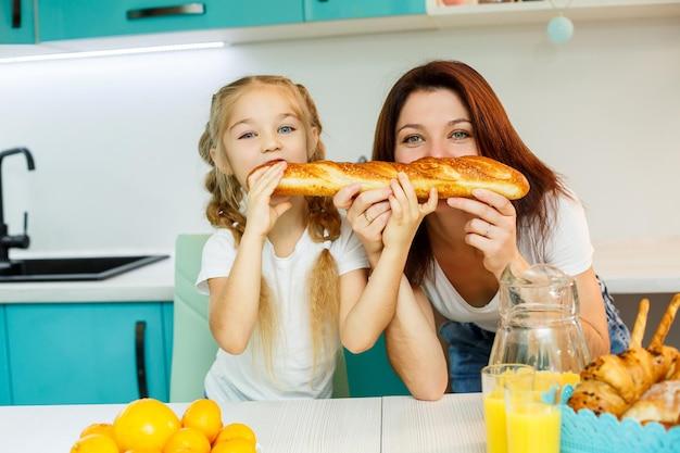 Gelukkige familie, moeder en dochter eten een brood dat van verschillende kanten bijt. familierelaties van het kind met de ouders