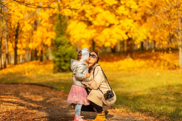 Gelukkige familie moeder en dochter in modieuze kleding lopen in het park en zoenen in een prachtig herfstpark met geel herfstgebladerte op een zonnige dag