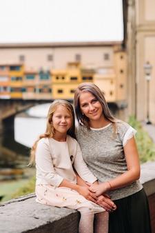 Gelukkige familie moeder en dochter tegen de achtergrond van de ponte vecchio-brug in florence.familiewandeling van de familie in italy.toscane.