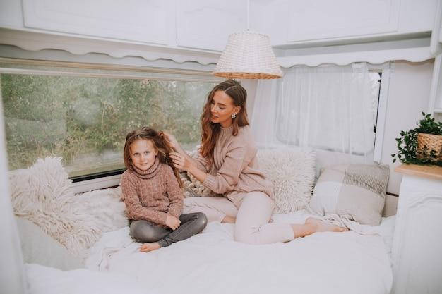 Gelukkige familie - moeder en dochtertje ontspannen knuffelen en plezier maken op het platteland