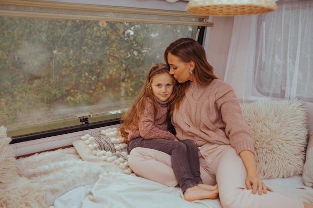 Gelukkige familie - moeder en dochtertje ontspannen op het platteland binnen witte scandinavische rustieke camper interieur.