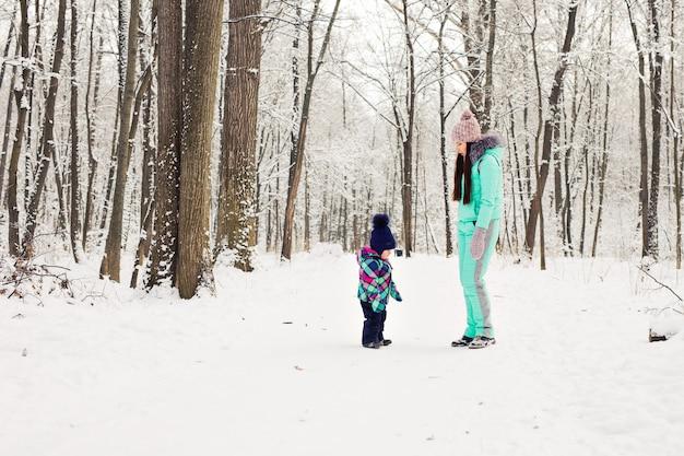 Gelukkige familie moeder en kind baby dochter op een winterwandeling in het bos.