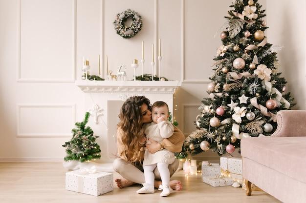 Gelukkige familie moeder en kind dochter op kerstochtend bij de kerstboom met geschenken