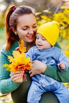 Gelukkige familie moeder en kind dochter spelen en lachen op herfstwandeling