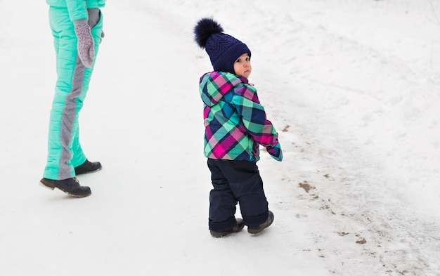 Gelukkige familie moeder en kind dochtertje op een winterse wandeling in het bos