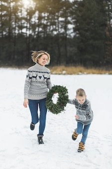 Gelukkige familie moeder en kind zoon in spijkerbroek en gebreide truien, hardlopen en plezier maken