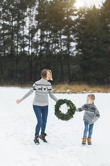Gelukkige familie moeder en kind zoon in spijkerbroek en gebreide truien op een wandeling, hardlopen en plezier maken