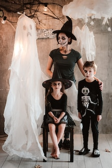 Gelukkige familie moeder en kinderen in kostuums en make-up op de viering van halloween
