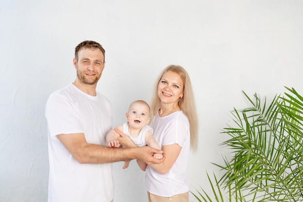 Gelukkige familie moeder en vader houden baby in hun armen tijdens het spelen en plezier maken thuis