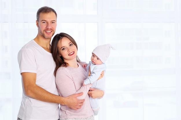 Gelukkige familie, moeder en vader staan met baby thuis in witte kamer in de buurt van raam.