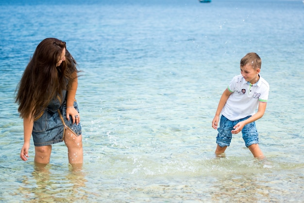 Gelukkige familie moeder en zoon staan in de zomer voor de zee