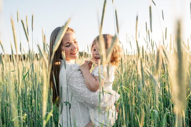 Gelukkige familie, moeder in een jurk met een schattige kleine baby op een gouden tarweveld bij zonsondergang. zomerdag.