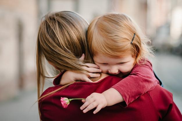 Gelukkige familie: moeder knuffel dochter met boeket bloemen genieten van tijd samen, staan op de straat stad in het land europa.