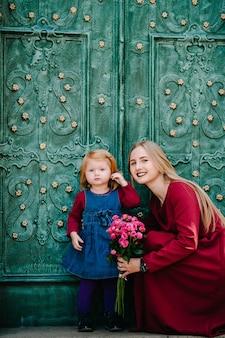 Gelukkige familie: moeder knuffel dochter met boeket bloemen genieten van tijd samen, staan op de straat stad in land europa.