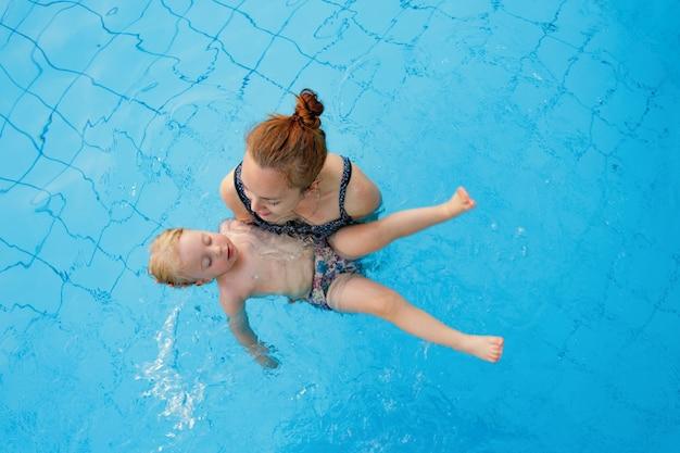Gelukkige familie moeder leert haar dochter jaar oud om te zwemmen in het bovenaanzicht van het zwembad