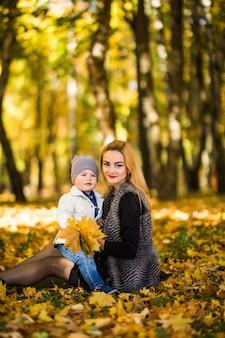 Gelukkige familie moeder spelen met kind in herfst park in de buurt van boom liggend op gele bladeren. herfst concept.
