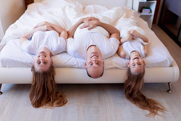 Gelukkige familie, moeder, vader, dochter lachen in bed in de slaapkamer thuis