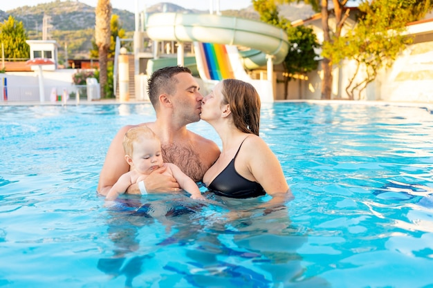 Gelukkige familie moeder, vader en baby dochter zwemmen in het zwembad met glijbanen en hebben plezier op vakantie, zoenen en knuffelen