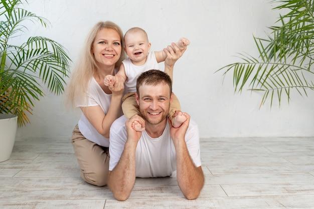 Gelukkige familie moeder vader en baby knuffelen en lachen, jonge ouders thuis veel plezier