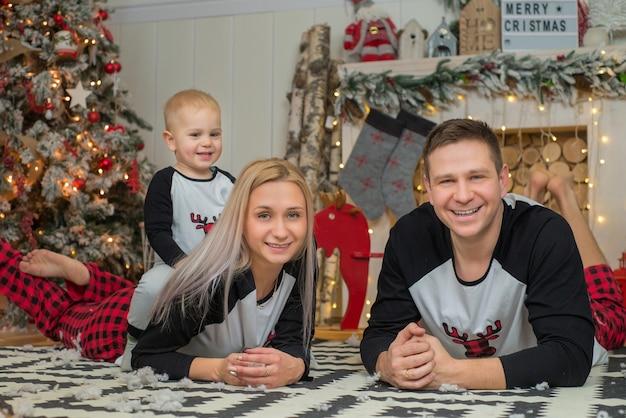 Gelukkige familie moeder, vader en baby met kerstmis