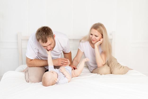 Gelukkige familie moeder vader en baby thuis met plezier, baby kruipen op de voorgrond