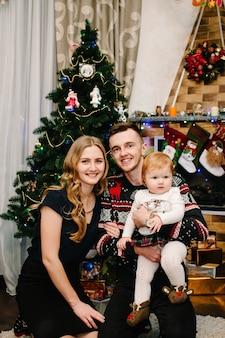 Gelukkige familie moeder, vader en dochter in de buurt van kerstboom met geschenken en open haard. vrolijk kerstfeest.