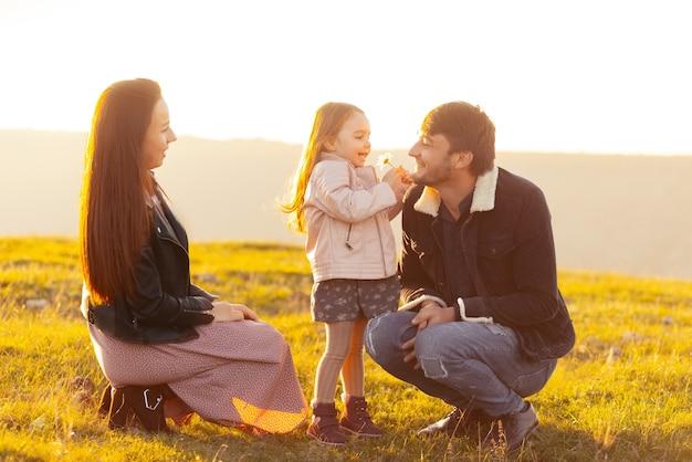 Gelukkige familie, moeder, vader en dochter met tijd samen op de natuur, in ingediend op zonsondergang